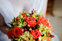 Wedding gold rings on a red and yellow bouquet Royalty Free Stock Image