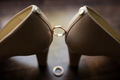 Wedding golden ring between the bride`s shoes on a dark background. stock photography