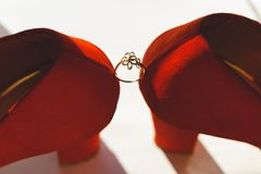 Wedding golden ring between the bride`s shoes on a light background.  Royalty Free Stock Photo