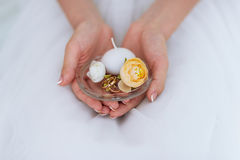 Wedding golden rings and candle on a palm at the bride. royalty free stock images