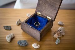 Wedding rings inside the open wooden box with stones around. Ceremony stock photos