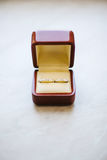 Wedding Golden Rings in red box on White. Wedding rings in wooden box on white. Golden identical elegant female and male rings. Jewelry in square container stock image