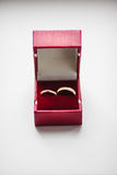 Wedding Golden Rings in red box on White. Wedding rings in wooden box on white. Golden identical female elegant ring with brilliant and male one. Jewelry in stock photo