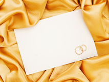 Wedding golden textile border. Golden silk textile border round white paper with golden rings stock image