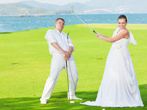 Wedding golf. Bride and groom are playing golf at wedding day Royalty Free Stock Photo