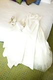 Wedding gown on bed Stock Photos
