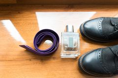 Wedding groom's accessories. Perfume in glass bottle, purple necktie, and a part of black shoes on a wooden background. Groom Stock Photos