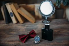 Wedding groom accessories, details of clothes, belt, wristwatch, boutonniere, bow-tie, perfume. Stock Photo