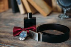 Wedding groom accessories, details of clothes, belt, wristwatch, boutonniere, bow-tie, perfume. Royalty Free Stock Image