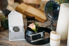 Wedding groom accessories, details of clothes, belt, wristwatch, boutonniere, perfume. Stock Images