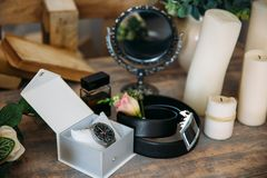 Wedding groom accessories, details of clothes, belt, wristwatch, boutonniere, perfume. Stock Photography