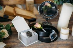 Wedding groom accessories, details of clothes, belt, wristwatch, boutonniere, perfume. Stock Photo