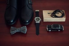 Wedding groom accessories, details of clothes, belt, wristwatch,. Close up of groom brown leather shoes, bowtie, belt and wristwatch . Modern man or groom Royalty Free Stock Image