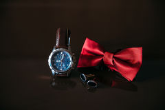 Wedding groom accessories, details of clothes, bow tie, cuff links, golden rings. Royalty Free Stock Image