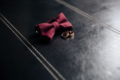 Wedding groom accessories, details of clothes, bow tie, golden rings. Stock Images