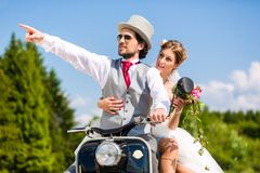 Bridal pair driving motor scooter wearing gown and suit Royalty Free Stock Images