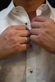 Wedding Groom buttoning shirt Stock Photos