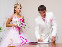 Wedding. The groom signs the registration documents royalty free stock photo