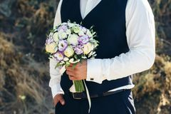 Wedding. The groom  in a white shirt  and waistcoat are holding bouquets of of white roses, hypericum, lisianthus, chrysanthemum, Royalty Free Stock Images