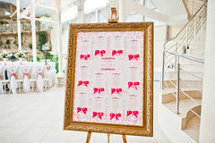 Wedding guest board with pink ribbons at wedding hall. Royalty Free Stock Photography