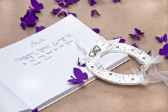 Wedding Guest Book with a Good Luck Horseshoe. Opened Wedding Guest Book with a Good Luck Horseshoe and Purple Butterflies on Beige Background Royalty Free Stock Photo