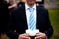 Wedding guest brings beer stock image