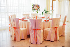 Wedding guest table decorated with bouquet and chairs with bows stock images