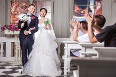 Wedding guests applauding for newlywed couple holding flowers in church.  stock photos