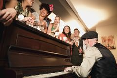 Wedding Guests Having Fun With The Piano. Wedding guests are enjoying a dance while the father of the bride plays piano music Royalty Free Stock Images