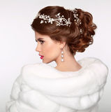 Wedding Hairstyle. Attractive girl in white fur coat. Jewelry Ea Stock Image