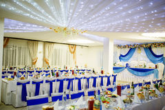 Wedding hall with chairs and table with blue ribbons. Royalty Free Stock Photography