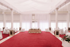 Wedding hall, decorated with red carpet and satin. Decorated layed tables Stock Photo