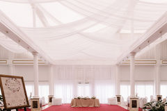Wedding hall, decorated with red carpet and satin. Decorated layed tables Royalty Free Stock Images