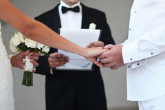 Wedding Hands. A bride and groom hold hands as a priest performs a wedding ceremony Royalty Free Stock Image