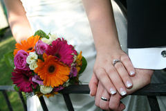 Wedding Hands 2. A bride and Groom's hands with bouquet of flowers on a rail Royalty Free Stock Photo