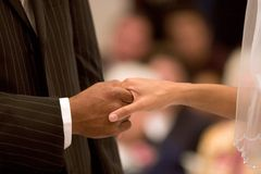 Wedding Hands. Grasped hands of a young married couple during a wedding service Stock Image