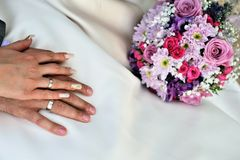 Wedding hands with bouquet Royalty Free Stock Image