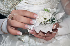 Wedding. Hands of a bride holding a wedding bouquet of white roses Stock Photography