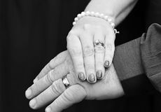 Wedding hands mature newlyweds couple isolated on black. A romantic and classic pose of hands of a mature couple just after they had their wedding ceremony Royalty Free Stock Photos