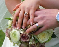 Wedding hands on posy. A couple`s hands on wedding flowers in England royalty free stock photography