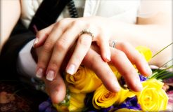 Wedding Hands Together. Bride and groom hands together on a flower bouquet Royalty Free Stock Photography