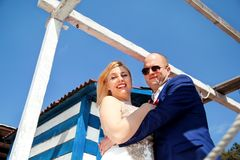 Wedding couple staying beside the blue white house. Wedding. Happy couple day wedding. Beautiful bride and groom cuddled. Cheerful married couple standing and Stock Photos