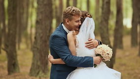 Wedding. Happy couple in a forest in the fresh air. Elegant groom behind bride. In the hands of a beautiful bouquet of stock footage