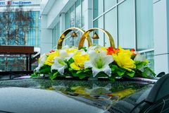 Wedding rings among flowers on the top of a wedding car stock image