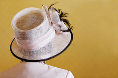 Wedding Hat. A women wearing a trendy hat on a plain yellow background - easy to isolate royalty free stock photography