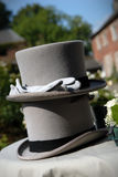 Wedding hats and gloves. Two grey wedding hats are stacked on each other, with a pair of pale grey gloves placed on the brim of the top one Stock Photos