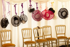 Wedding Hats. Weddings hats hanging from a ribbon above chairs Royalty Free Stock Photography