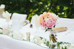 Wedding Head Table Decor. A romantic garden wedding reception head table with a pink and gold color scheme. Mirror and peony bouquet details. Horizontal Royalty Free Stock Photography