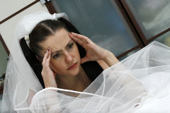 Wedding headache. The headache is represented on the face of the beautiful bride in a wedding dress near a bed Stock Image