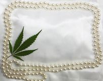 Wedding hippie original bridal satin white background with pearls frame and marijuana pressed leaf in corner. Invitation card, fre. Edom ganja backdrop design royalty free stock photography
